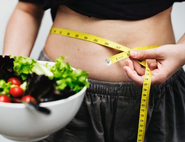 femeie la dieta Rina care își măsoară talia cu un centimetru