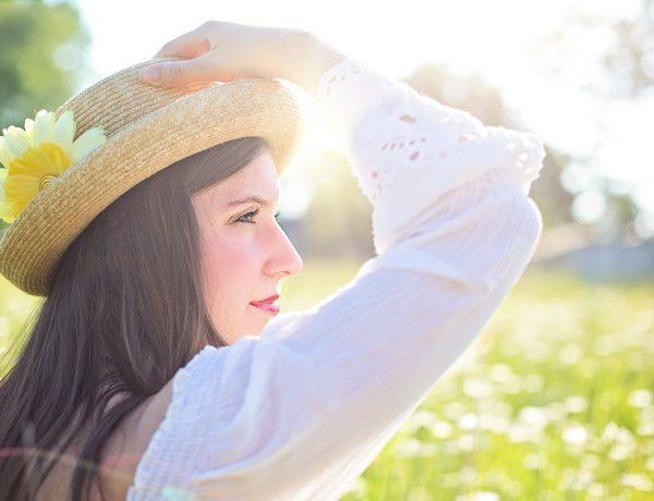 Femeie care se protejează de insolație cu o pălărie