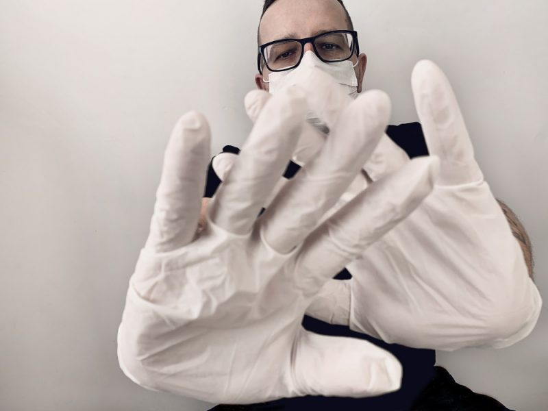 Barbat cu ochelari care poarta masaca si manusi albe chirurgicale pentru a se feri de coronavirus