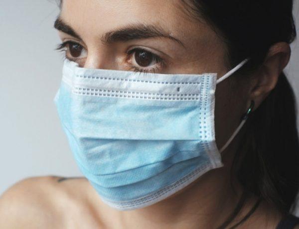 Fata care poarta o masca medicala albastra, de unica folosinta, pentru a se proteja impotriva coronavirusului