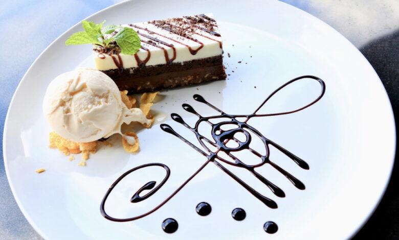 Prajitura Brownie cu topping alb si inghetata, pe o farfurie alba cu portativ desenat cu sos