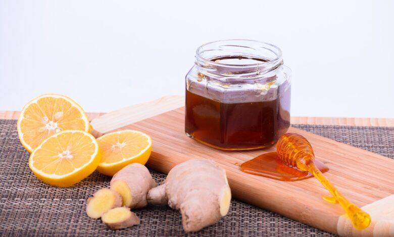 Borcan cu miere pe fund de lemn lingurita ghimbir lamaie