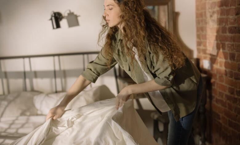 Femeie care schimba asternuturile si face curat in casa