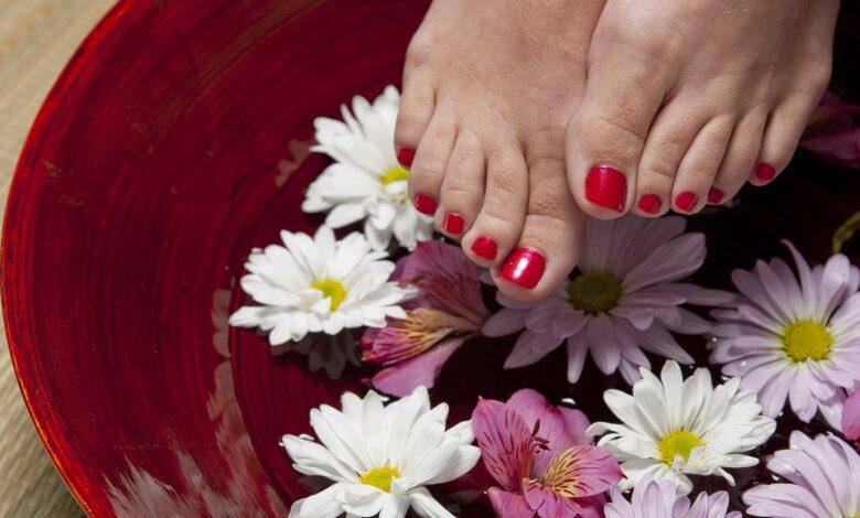 Picioarele umflate ale unei femei intr-un lighean cu bicarbonat de sodiu si flori