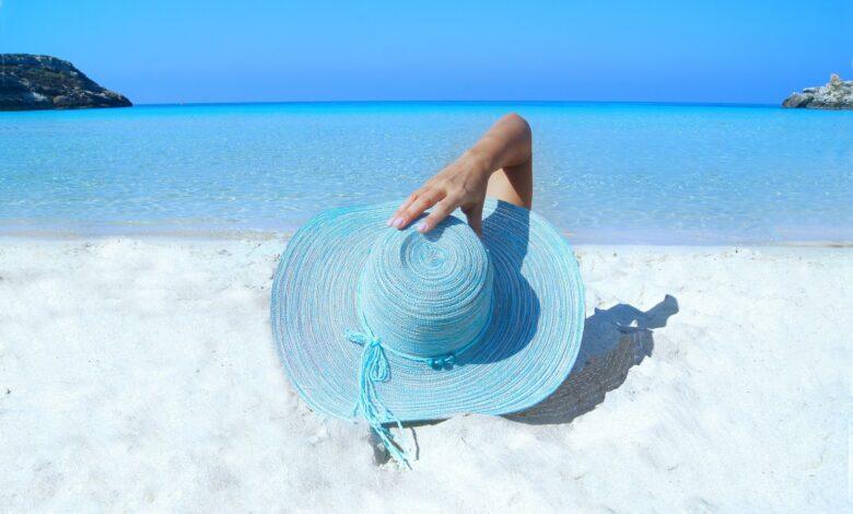 Femeie cu palarie pe cap care face plaja pe malul marii