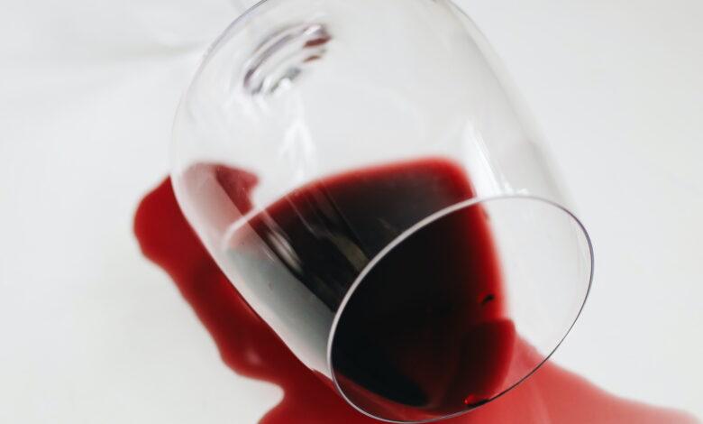 Pahar cu vin rosu rastunat care lasa pete pe fata de masa